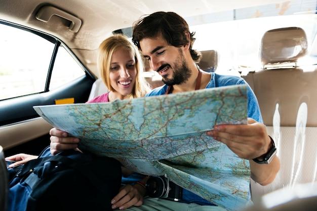 Hombre sosteniendo un mapa mostrando a su novia su próxima parada