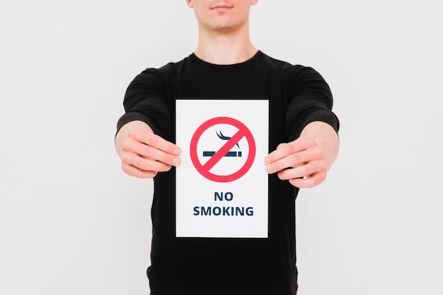 Hombre sosteniendo papel sin texto de fumar y firmar en pared blanca