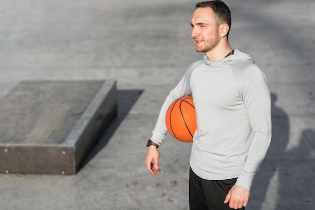 Hombre sosteniendo una pelota de baloncesto y mirando a otro lado