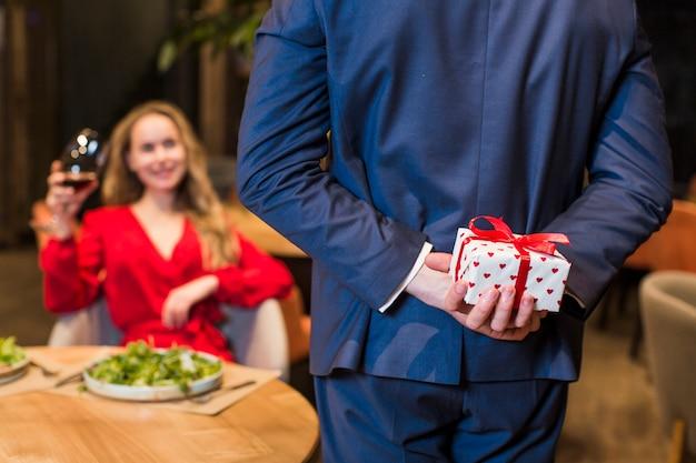 Hombre sosteniendo una pequeña caja de regalo detrás de la espalda