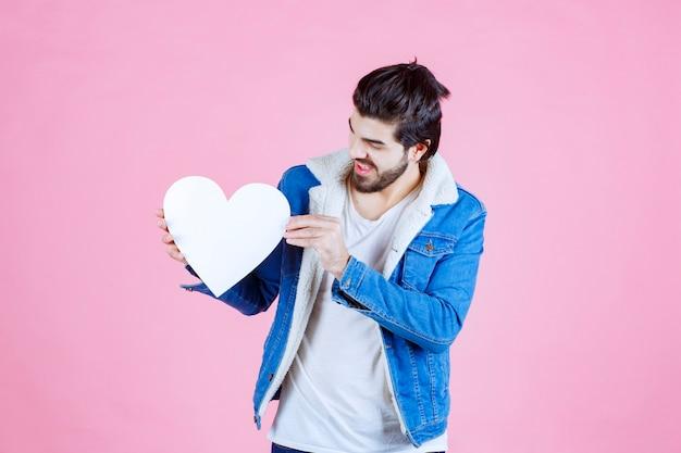 Hombre sosteniendo y presentando una figura de corazón en blanco con sonrisas