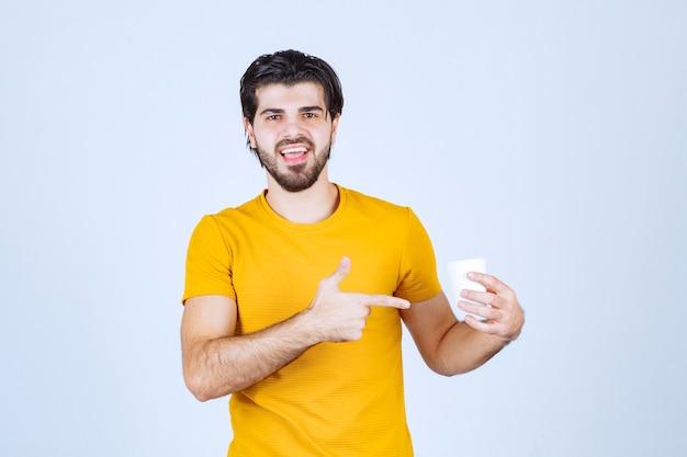 Hombre sosteniendo y promocionando una taza de café.