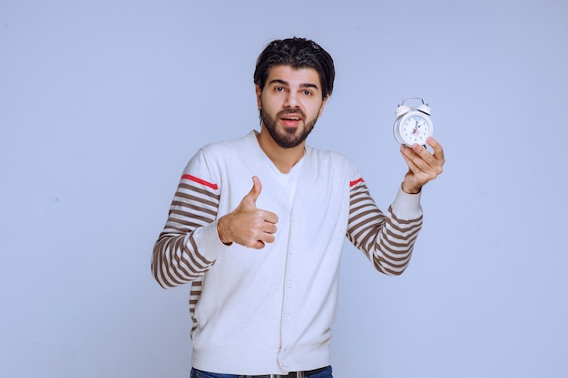 Hombre sosteniendo un reloj despertador y haciendo pulgar hacia arriba.