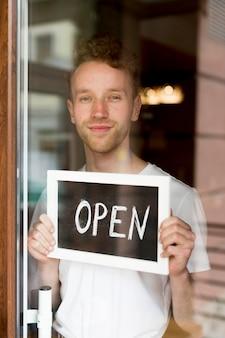 Hombre sosteniendo señal abierta