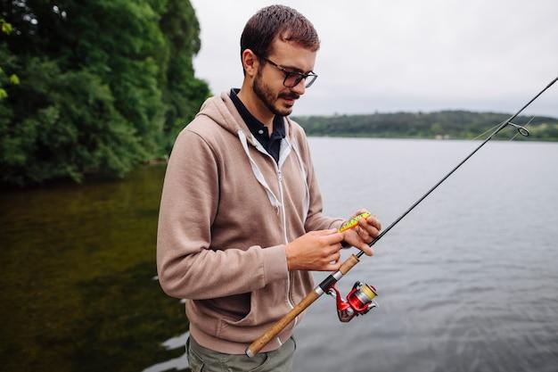 Hombre sosteniendo señuelo y caña de pescar cerca del lago