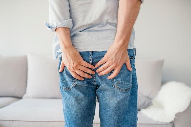 Hombre sosteniendo su parte inferior en el dolor, aislado en gris