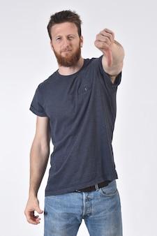 Hombre sosteniendo su pulgar hacia abajo y serio en blanco, serio