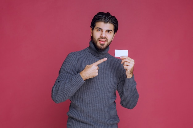 Hombre sosteniendo su tarjeta de visita y apuntando a ella.