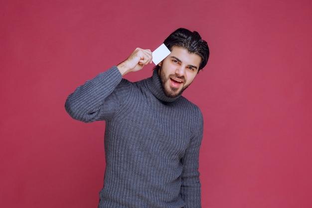 Hombre sosteniendo su tarjeta de visita, sintiéndose muy positivo y seguro de sí mismo.