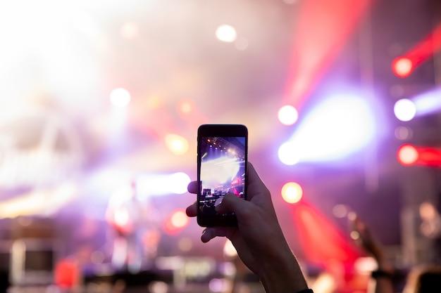 Hombre sosteniendo su teléfono inteligente y fotografiando concierto.