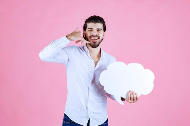 Hombre sosteniendo un tablero con forma de nube y pidiendo una llamada.