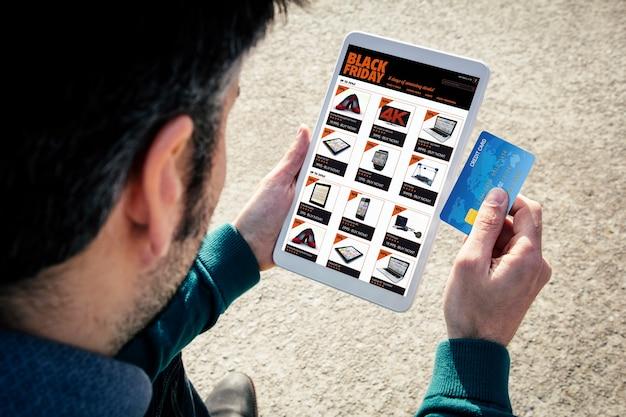 Hombre sosteniendo una tableta y compras en línea el viernes negro con tarjeta de crédito
