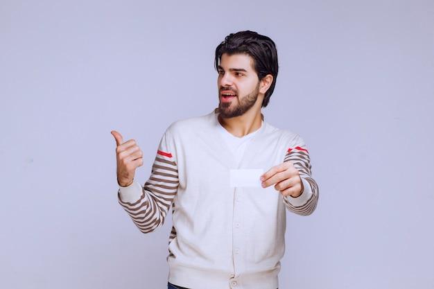 Hombre sosteniendo una tarjeta de visita y mostrando el pulgar hacia arriba.