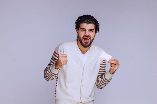 Hombre sosteniendo una tarjeta de visita y mostrando su puño.