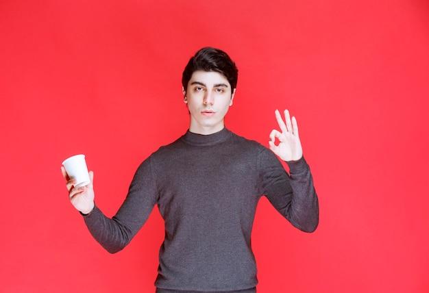 Hombre sosteniendo una taza de café y mostrando signos positivos