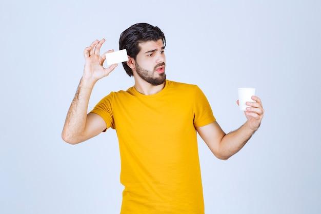 Hombre sosteniendo una taza de café y presentando su tarjeta de visita.