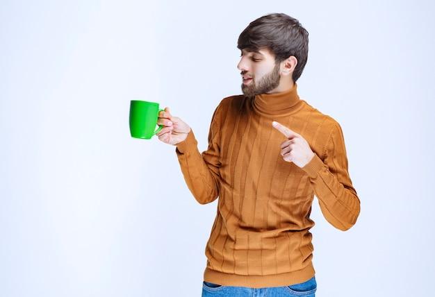 Hombre sosteniendo una taza verde y apuntando a ella.