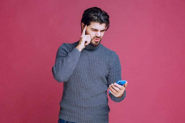 Hombre sosteniendo un teléfono inteligente y tratando de comprender sus funciones.
