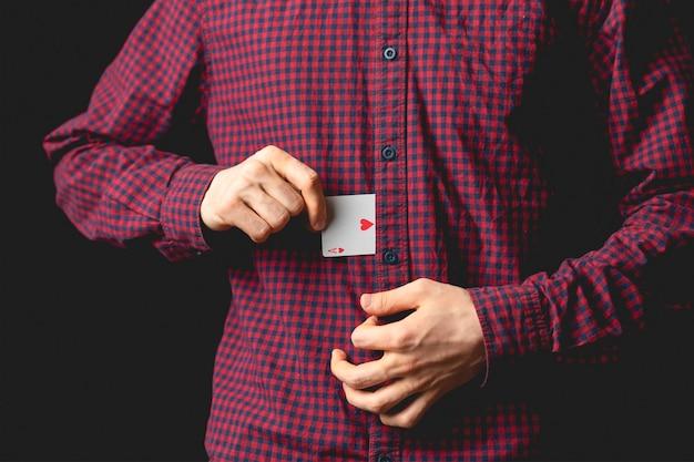 El hombre sostiene el as en la manga y hace trucos con las cartas b