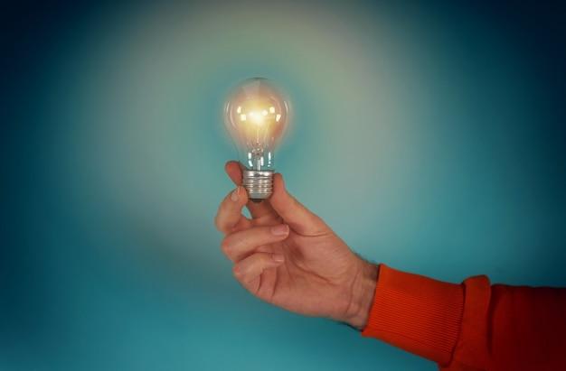 El hombre sostiene una bombilla en la mano concepto de creatividad y solución de fondo cian