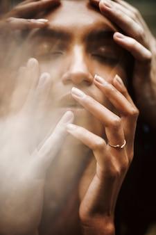 El hombre sostiene la cabeza de la mujer tierna mientras ella sostiene sus tiernos dedos en los labios.