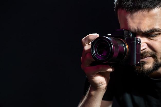 El hombre sostiene una cámara y está listo para disparar. el fotógrafo mira por el visor de la cámara y toma fotografías.