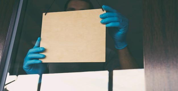 El hombre sostiene el cartel de madera con el texto: abierto para llevar y entregar