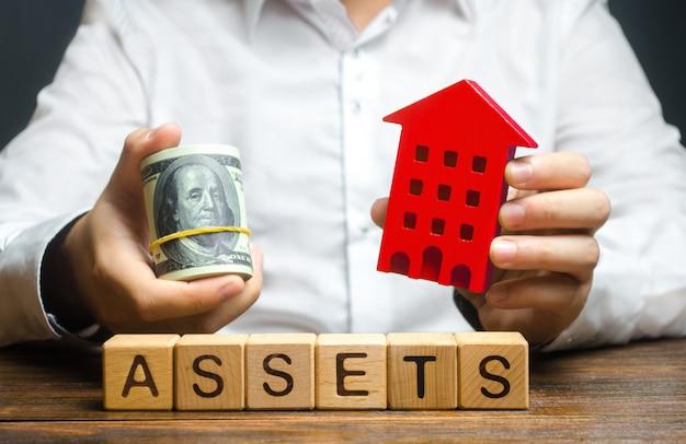 Un hombre sostiene una casa roja y un rollo de dólares sobre la palabra activos. declaración de ingresos e impuestos