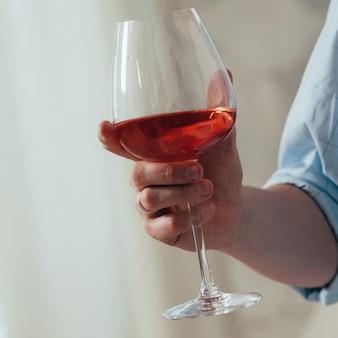 Un hombre sostiene una copa de vino tinto en la mano derecha.