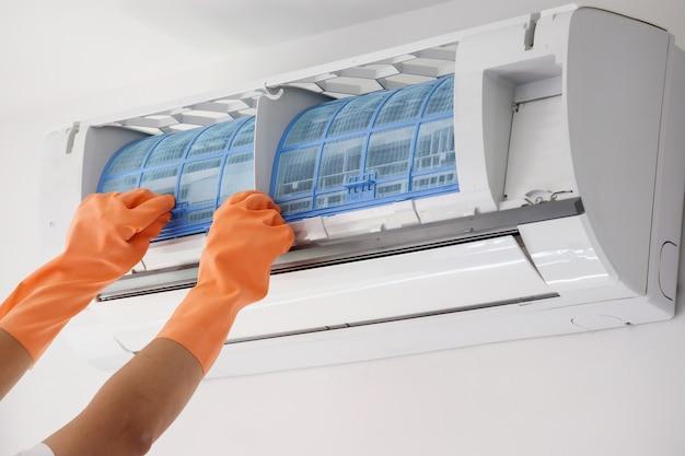El hombre sostiene el filtro de aire acondicionado
