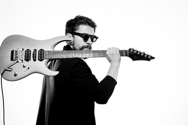 Un hombre sostiene una guitarra en sus manos con chaqueta de cuero negro y gafas oscuras sobre un fondo claro.