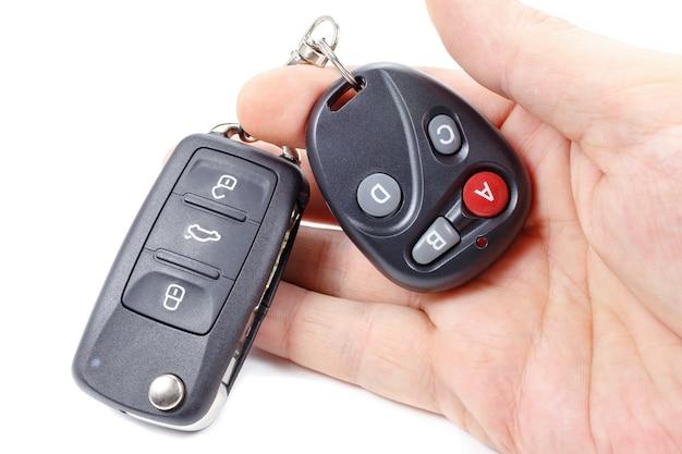 El hombre sostiene en la mano la llave de encendido y el control remoto de la puerta del garaje
