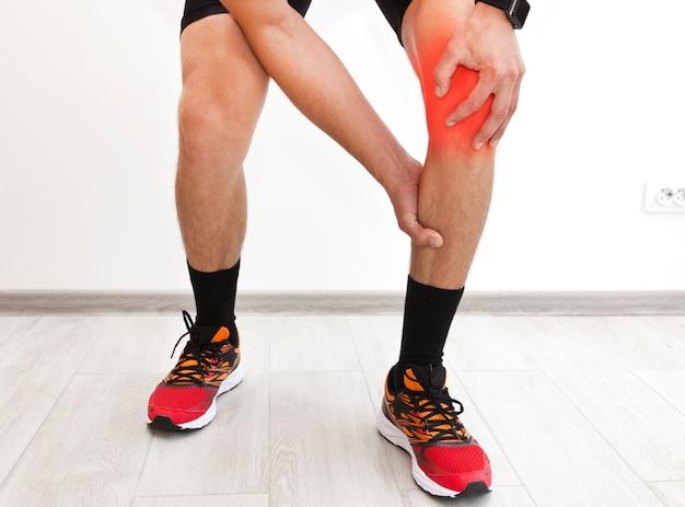 El hombre se sostiene y se masajea la pierna porque le quema después del entrenamiento.