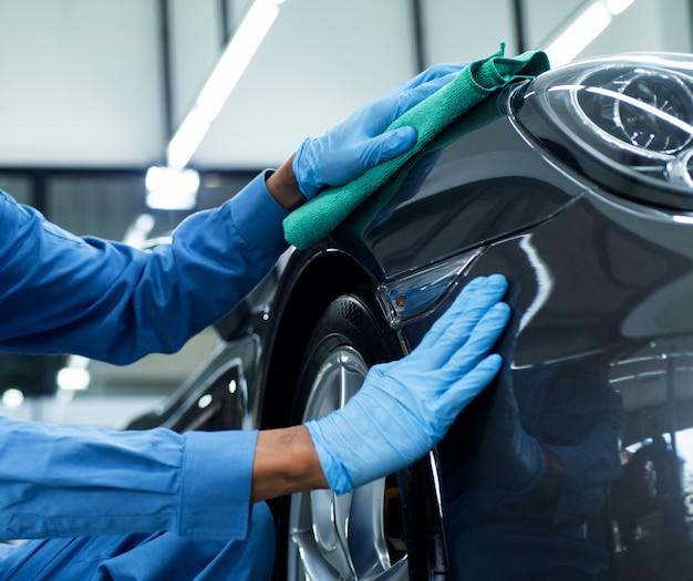 El hombre sostiene la microfibra en la mano y pule el auto