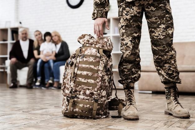 Un hombre sostiene una mochila y va a la guerra.