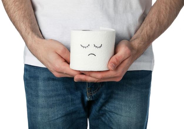 El hombre sostiene papel higiénico con cara triste, aislado en blanco