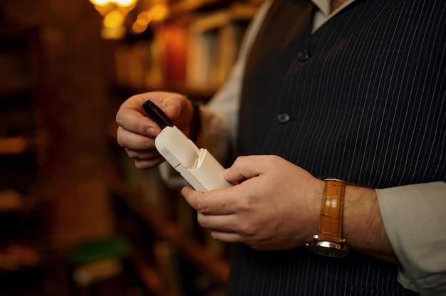 El hombre sostiene un paquete de cigarrillos y boquilla, estantería y un rico interior de oficina. cultura del tabaquismo, sabor específico. hábito de fumar