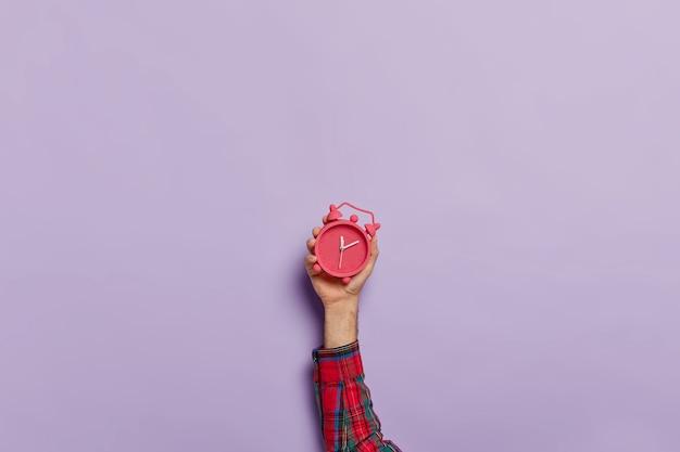 El hombre sostiene el pequeño despertador rojo en la mano