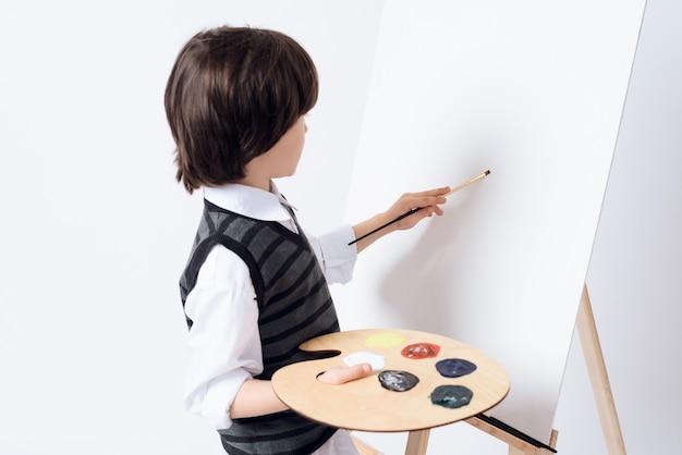 El hombre sostiene la pintura y el pincel en la mano.