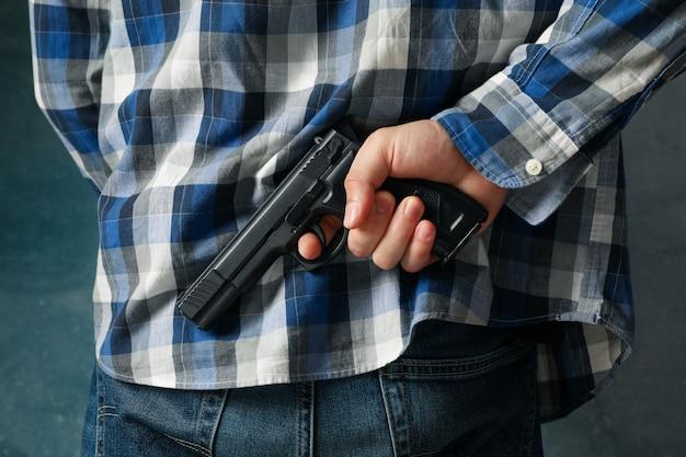 Un hombre sostiene una pistola por detrás. arma de autodefensa