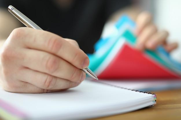 El hombre sostiene la pluma en la mano y escribe en el cuaderno