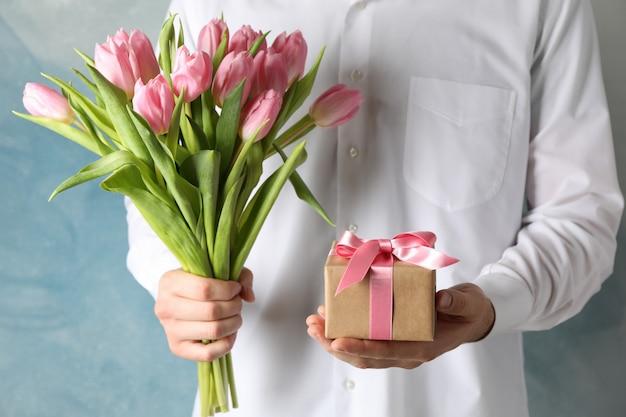 El hombre sostiene el ramo de tulipanes rosados y regalo en azul, primer plano