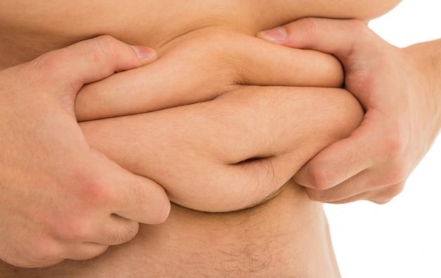 El hombre sostiene su barriga gorda