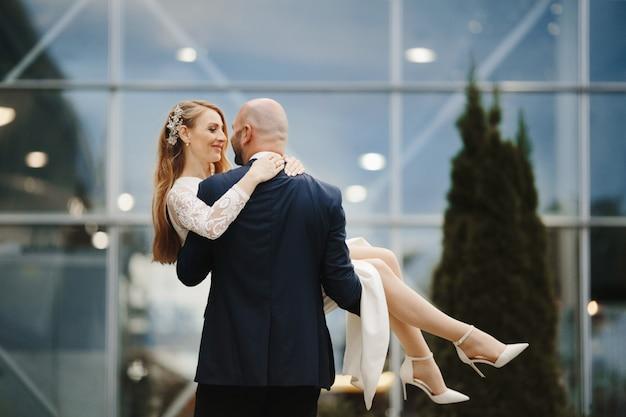 El hombre sostiene a su bella esposa en las manos