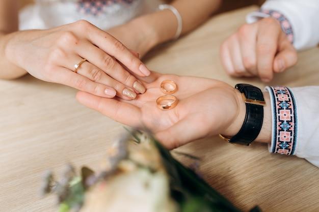 El hombre sostiene en su brazo dos anillos de boda dorados ante una mujer.