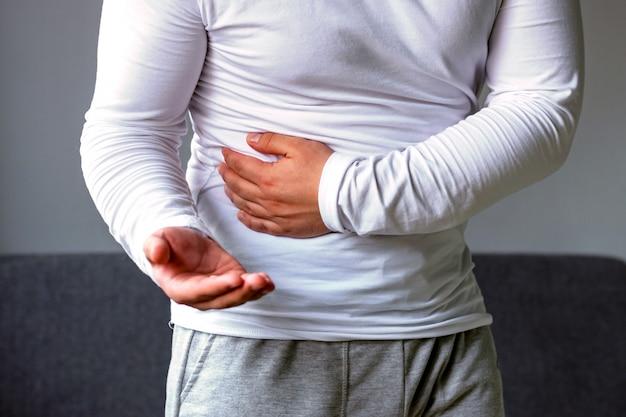 Un hombre sostiene su estómago, estira su mano con pastillas.