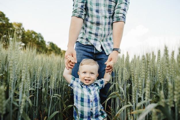 El hombre sostiene a su hijo por las manos entre el campo de trigo