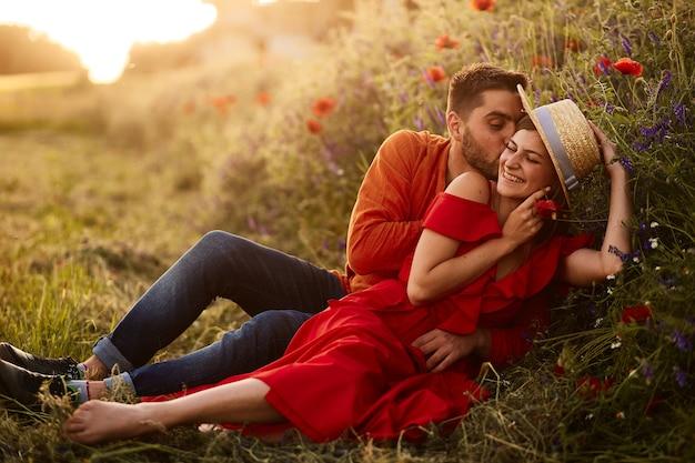 El hombre sostiene a su mujer tierna sentada con ella en el césped verde con amapolas rojas
