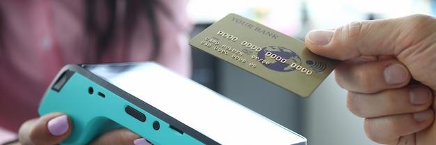El hombre sostiene la tarjeta de crédito sin contacto al terminal