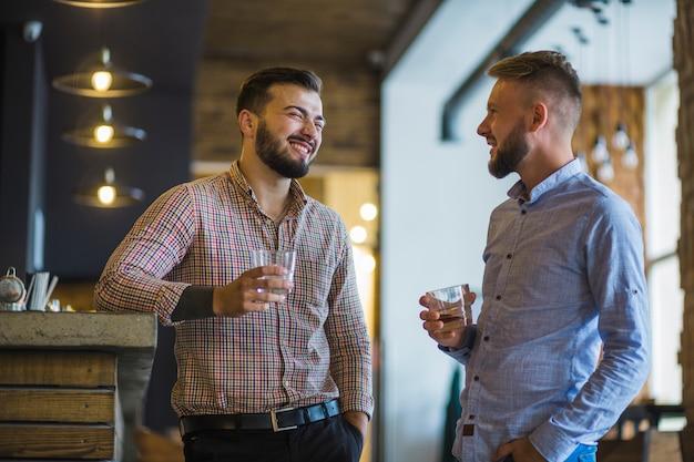 Hombre con su amigo sosteniendo un vaso de whisky en el bar